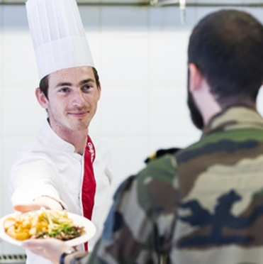 A chef serving food to a man in military uniform