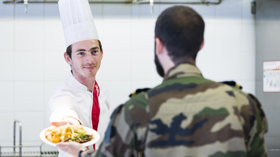 A sodexo employee handing clean uniforms to a member of the armed forces