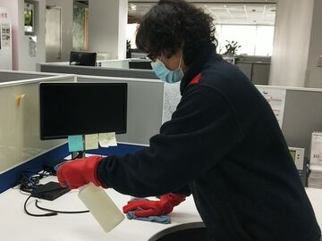 Sodexo staff cleaning office desks with disinfecting solution