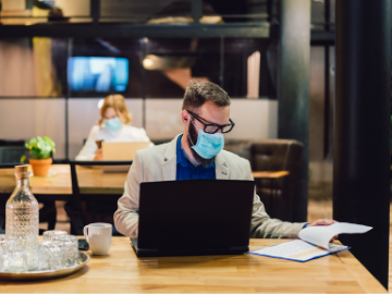 employees working in an office wearing masks sitting apart