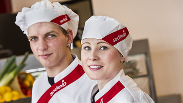 a male and female chef in sodexo uniform smiling at the camera