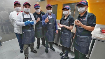 Group of people wearing aprons and Sodexo cap