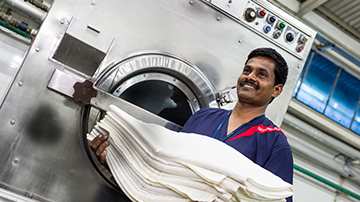 Sodexo employee folding laundry