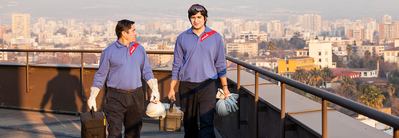 Two Sodexo employees standing on a roof in overalls, googles and hard hats